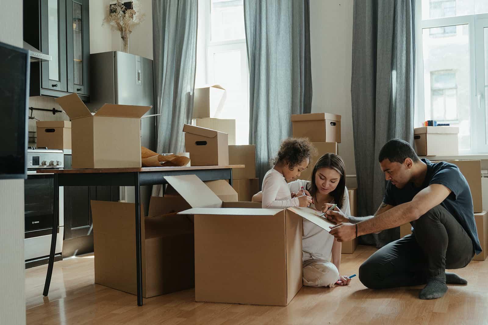Eine Familie packt Kisten aus, nachdem sie in eine neue Wohnung gezogen ist