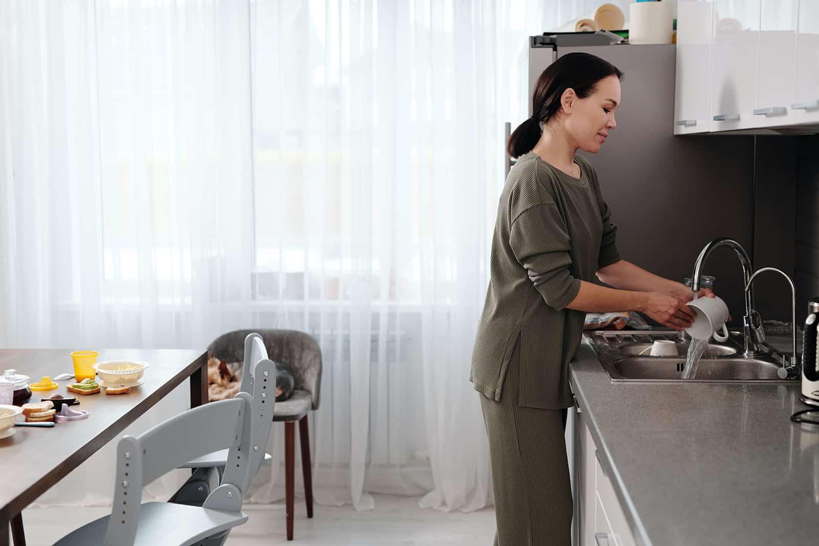 eine Frau, die Geschirr spült, um einem Freund zu helfen