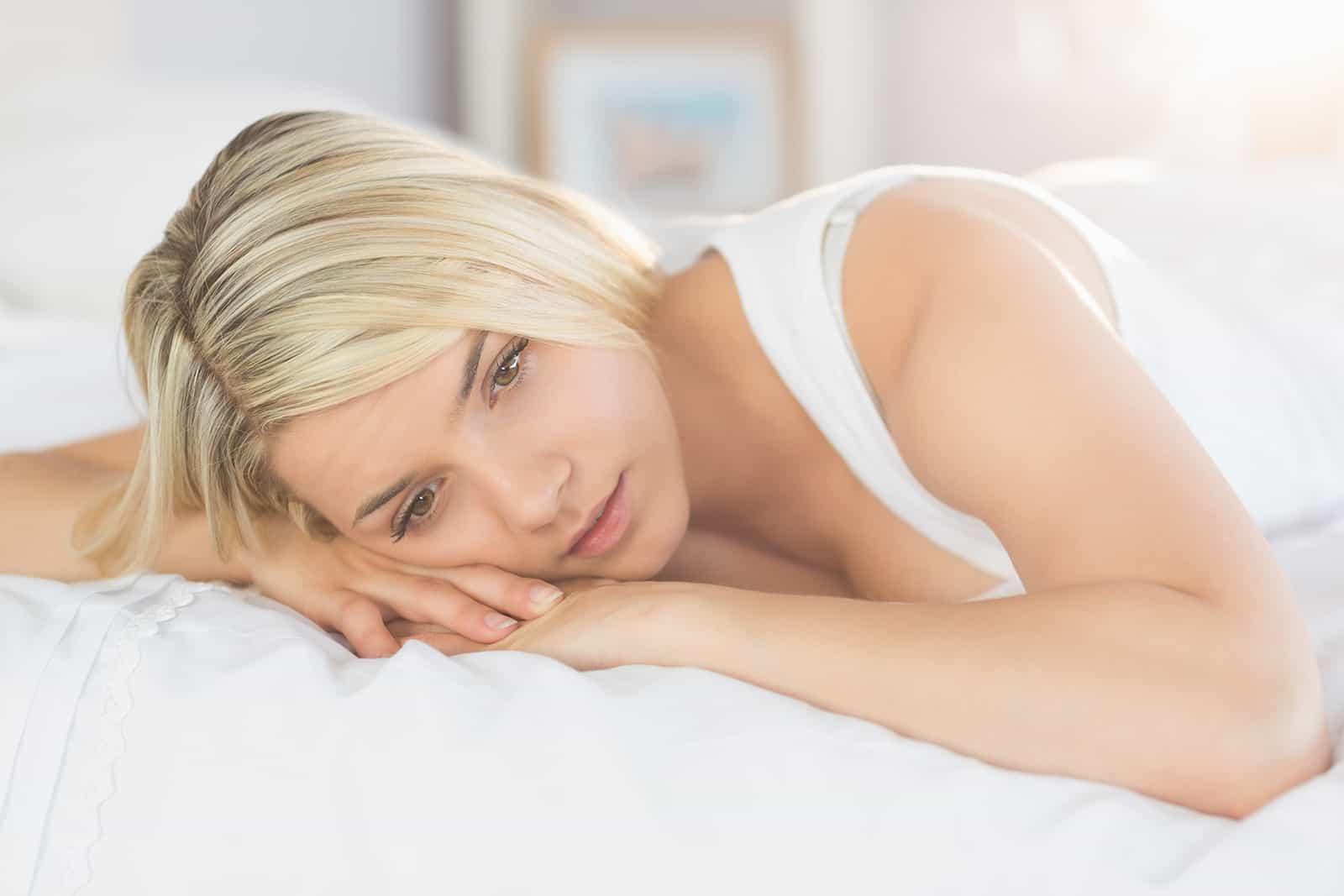 eine Frau, die auf dem Bett liegt und über ihr Leben nachdenkt
