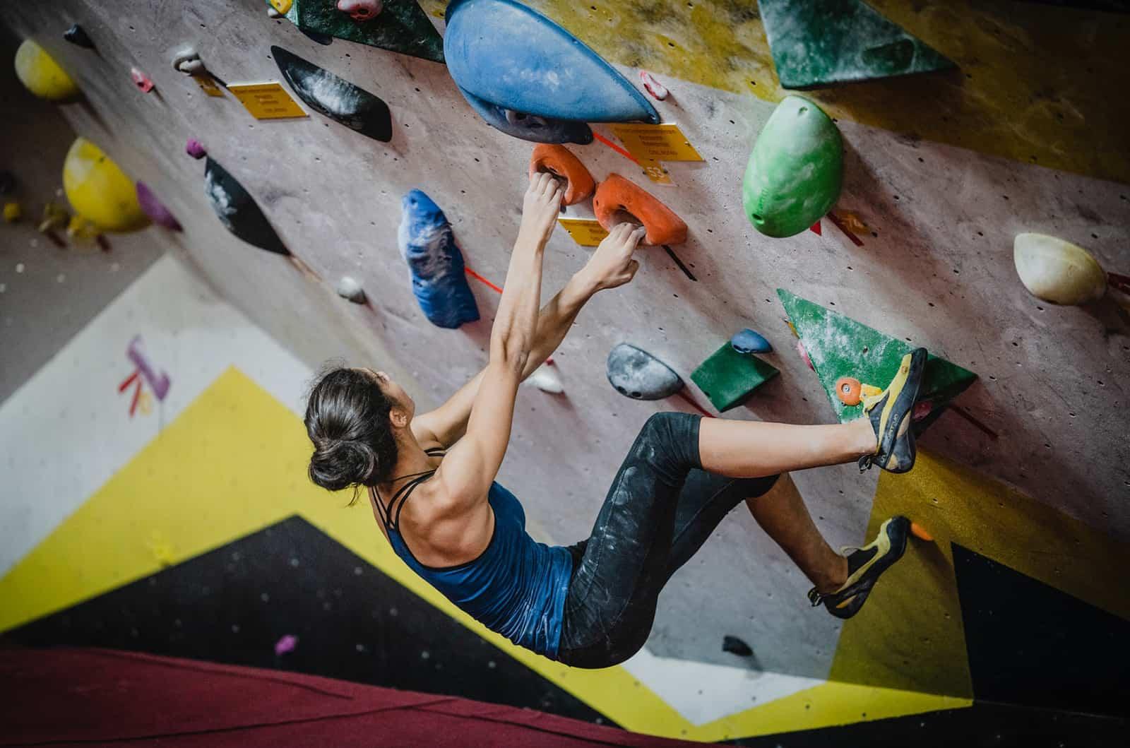 Eine Frau klettert auf die Felswand im Gebäude