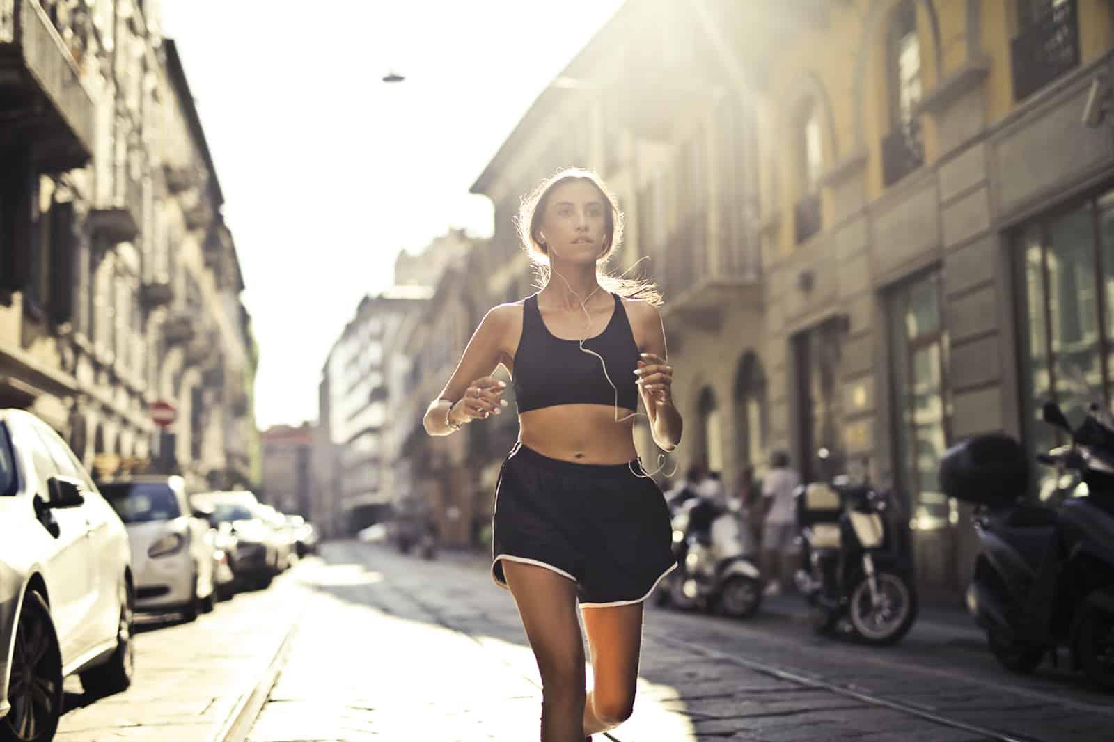 eine Frau, die die Straße entlang joggt und Musik über Kopfhörer hört