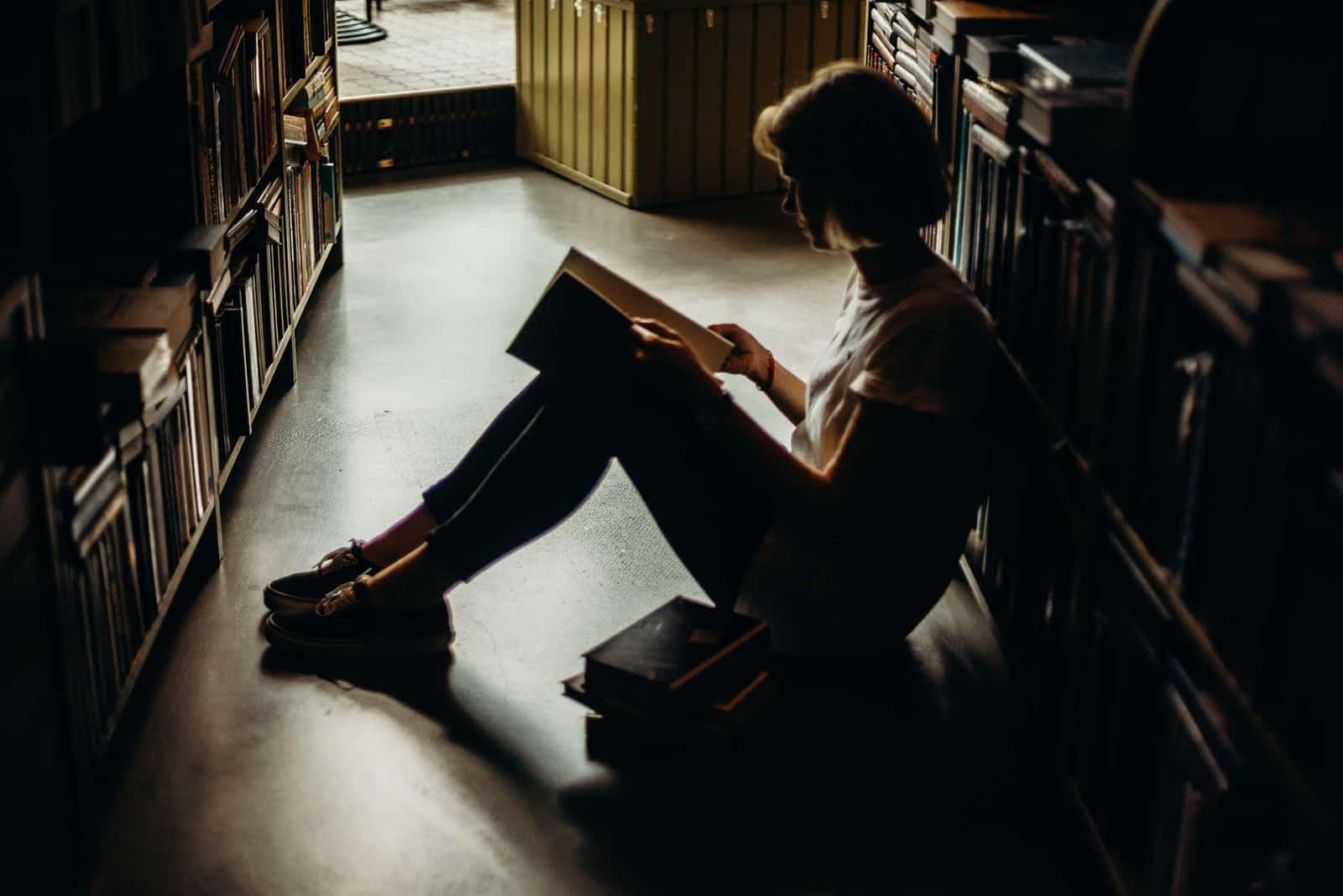eine Frau, die ein Buch liest, das auf dem Boden in der Bibliothek sitzt