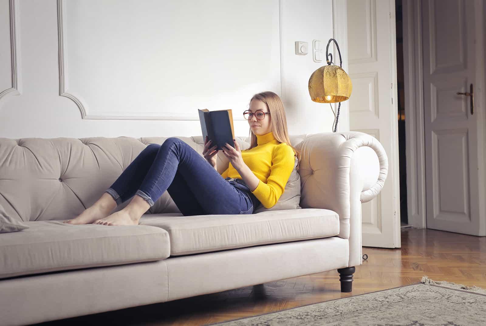eine Frau, die ein Buch liest, das auf der Couch sitzt