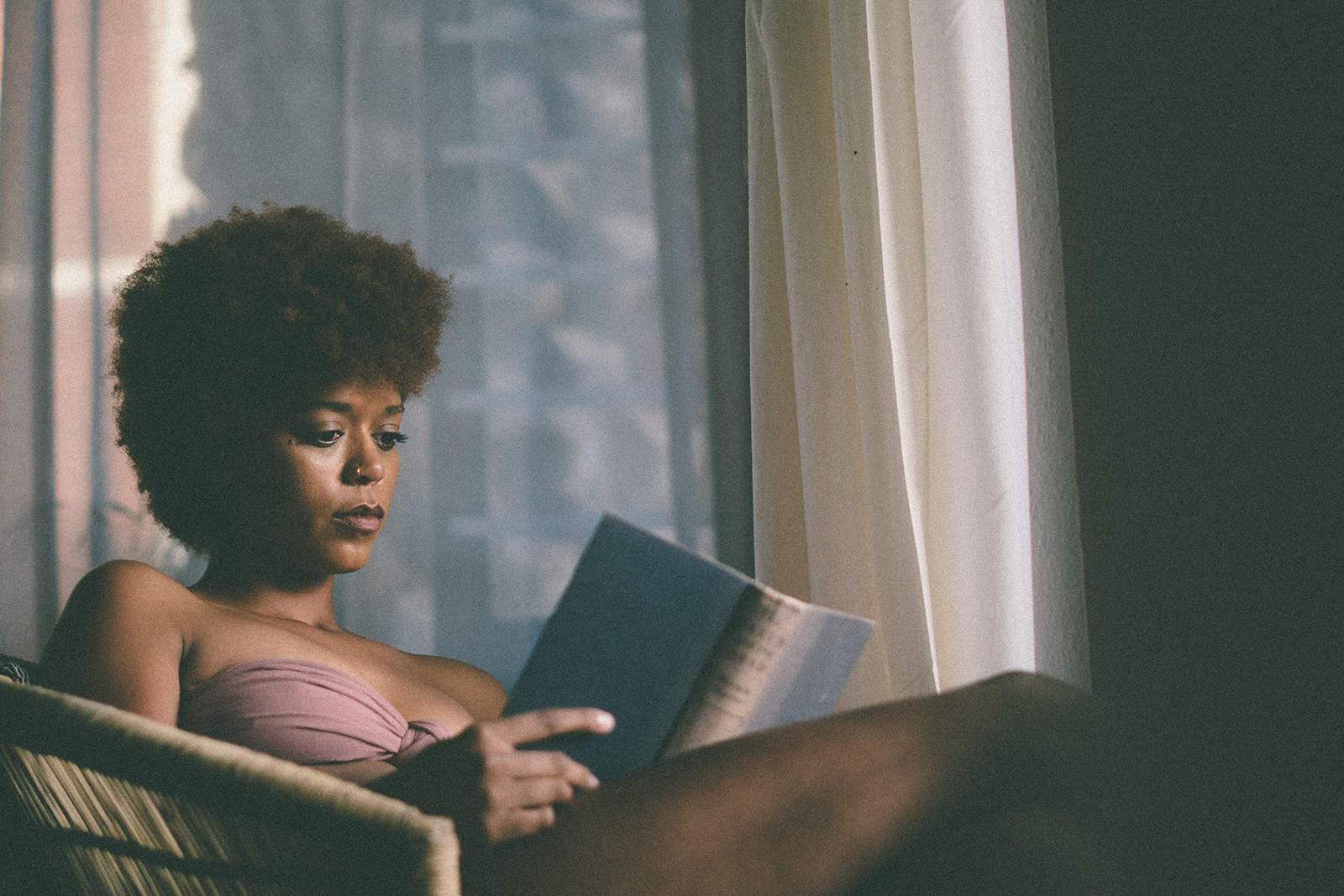 eine Frau, die ein Buch mit Gedichten liest, die im Sessel sitzen