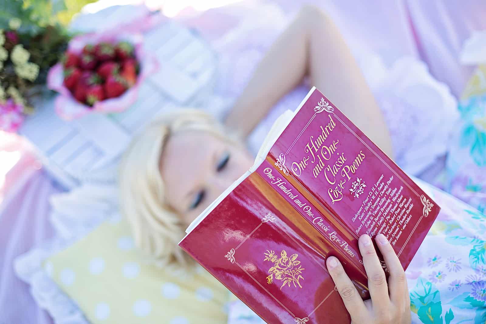 eine Frau, die ein Buch mit Liebesgedichten liest, während sie auf der Decke liegt