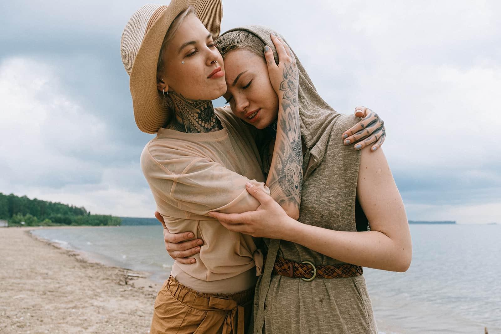 eine Frau, die eine Freundin tröstet, während sie am Strand steht