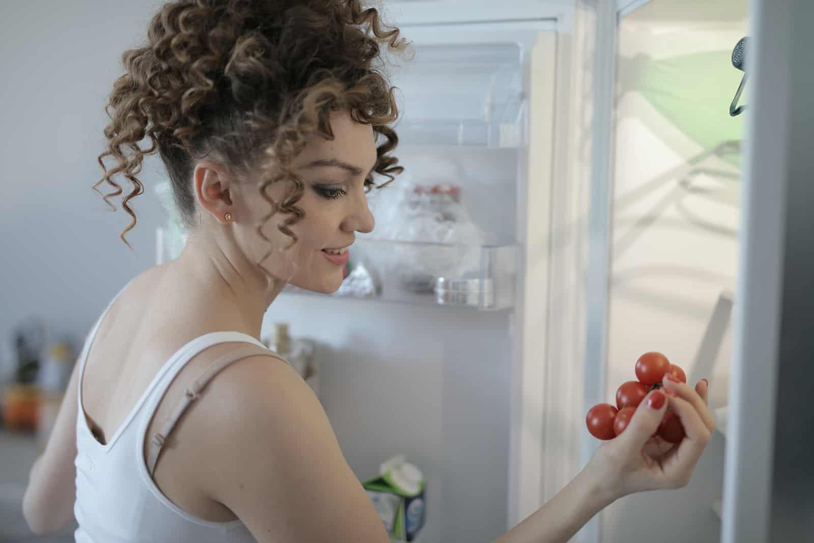 eine Frau, die eine Kirschtomate hält und in der Nähe des Kühlschranks steht