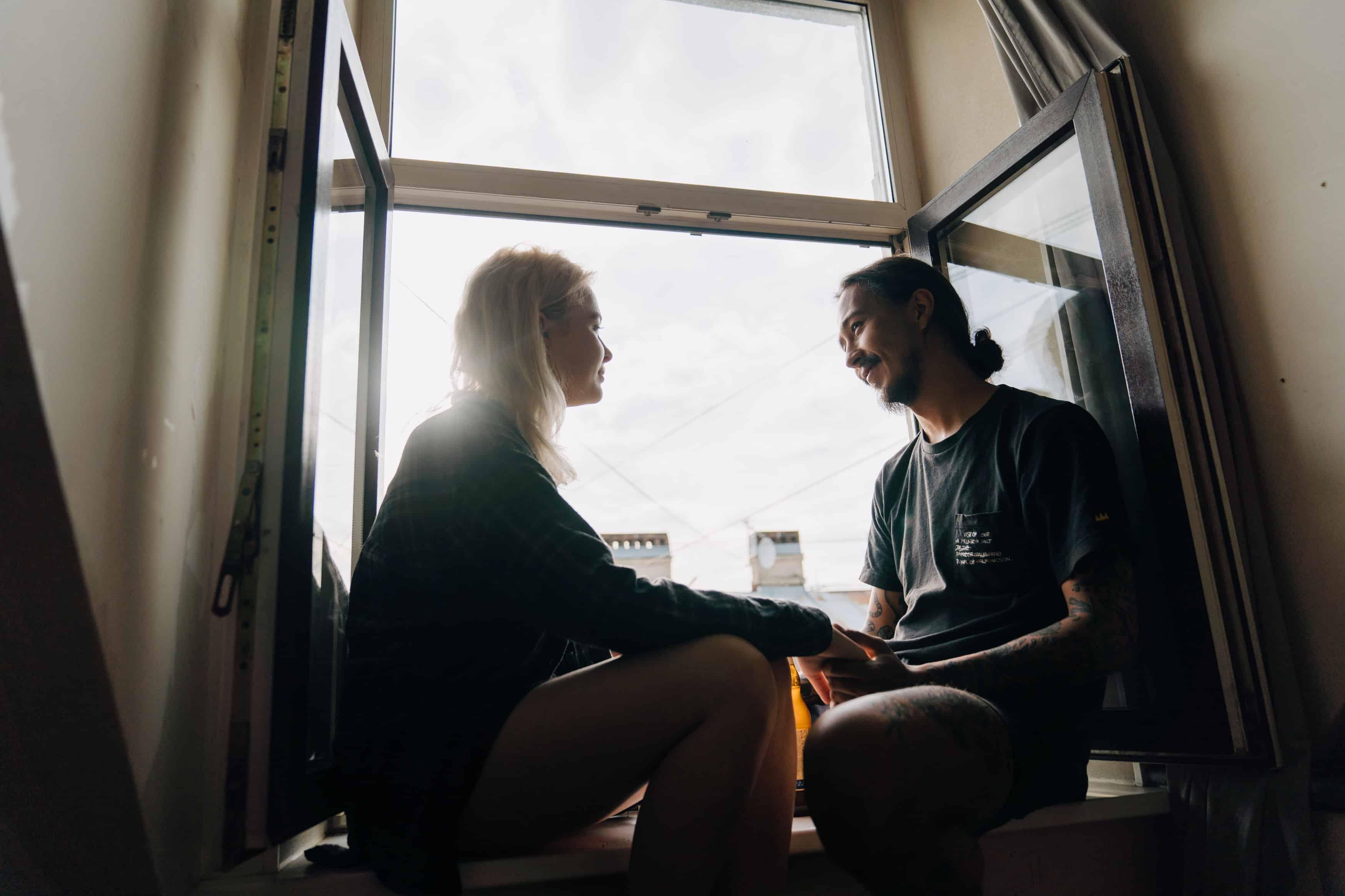 eine Frau, die einem Mann Dankbarkeit zeigt, während sie zusammen auf der Fensterbank sitzt