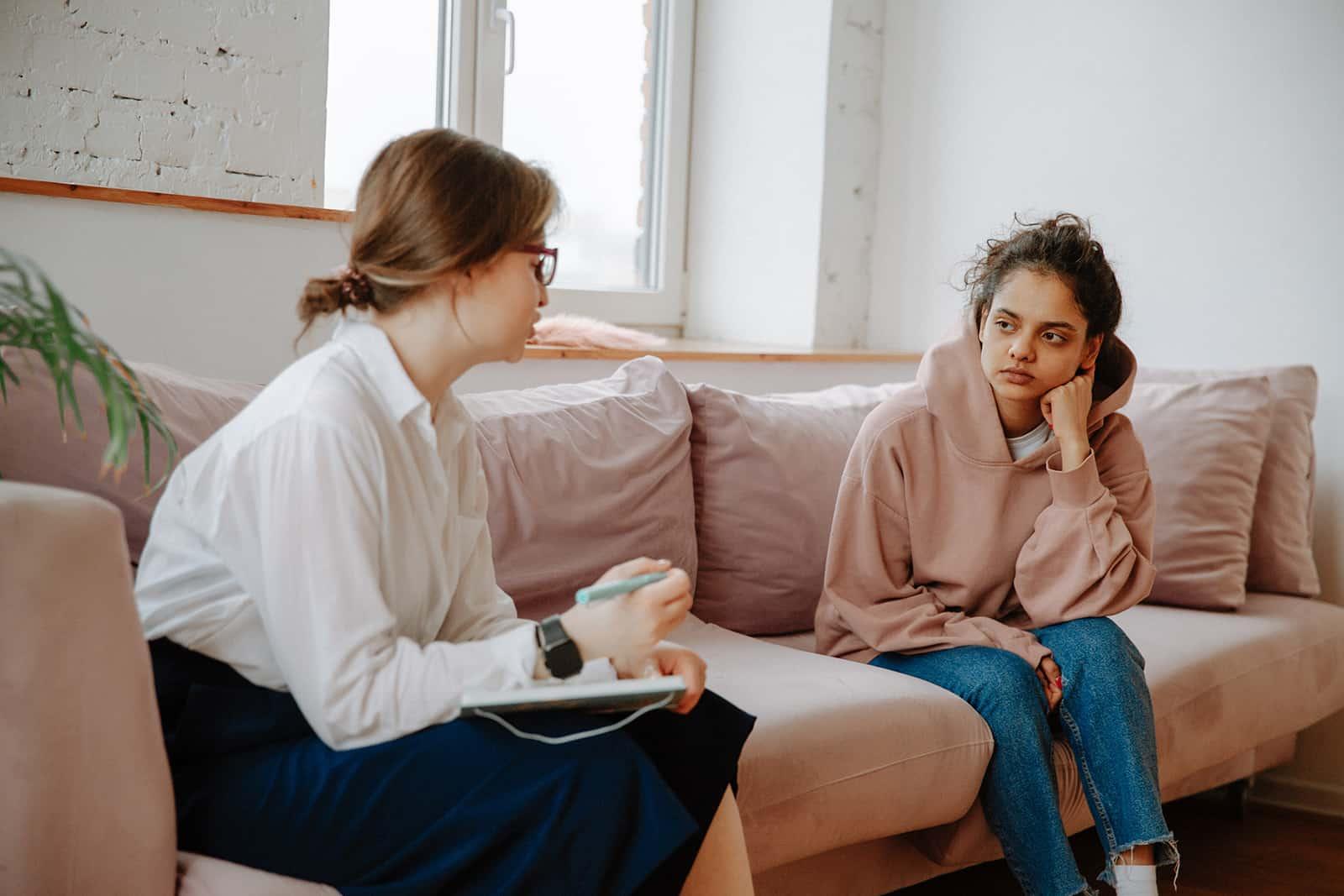 Eine Frau hört einem Therapeuten zu, der neben ihr auf der Couch sitzt