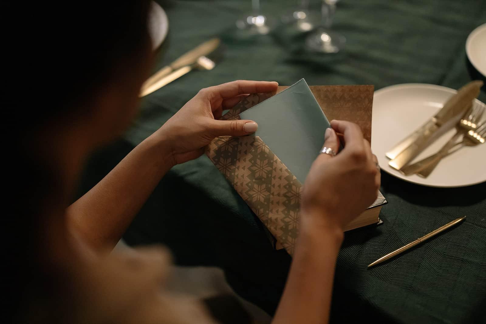 eine Frau, die einen Gutschein in einen Umschlag steckt, während sie am Tisch sitzt