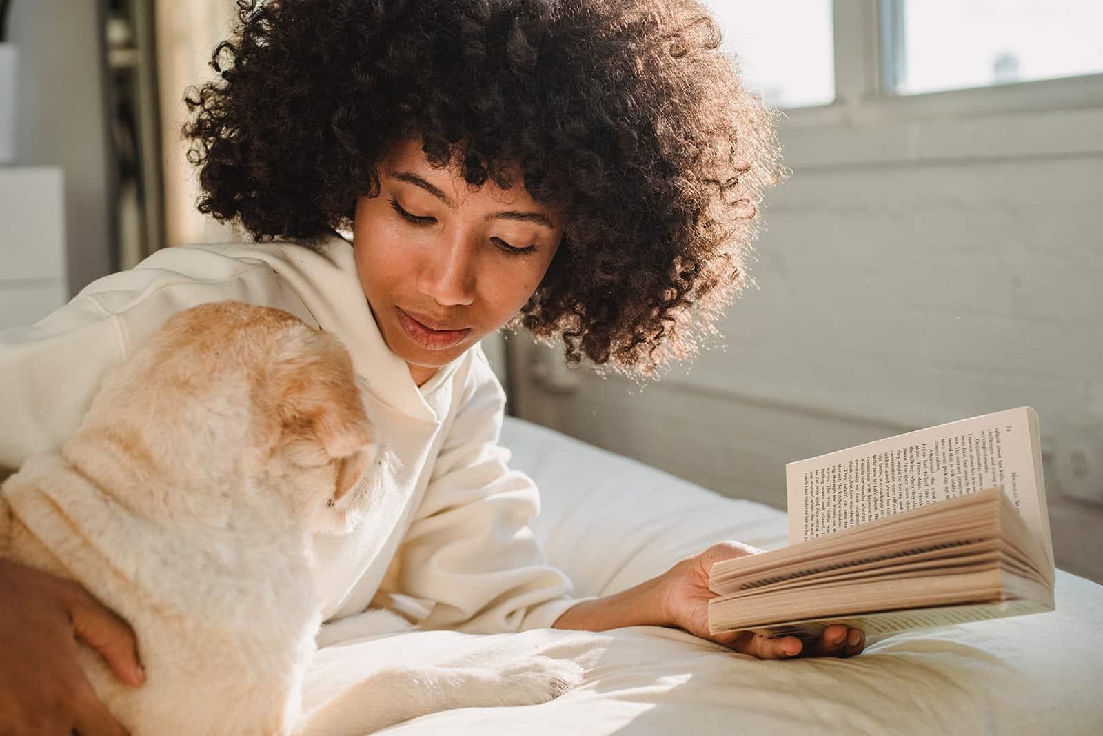 Eine Frau, die einen Hund streichelt, während sie ein Buch liest und auf einem Bett liegt