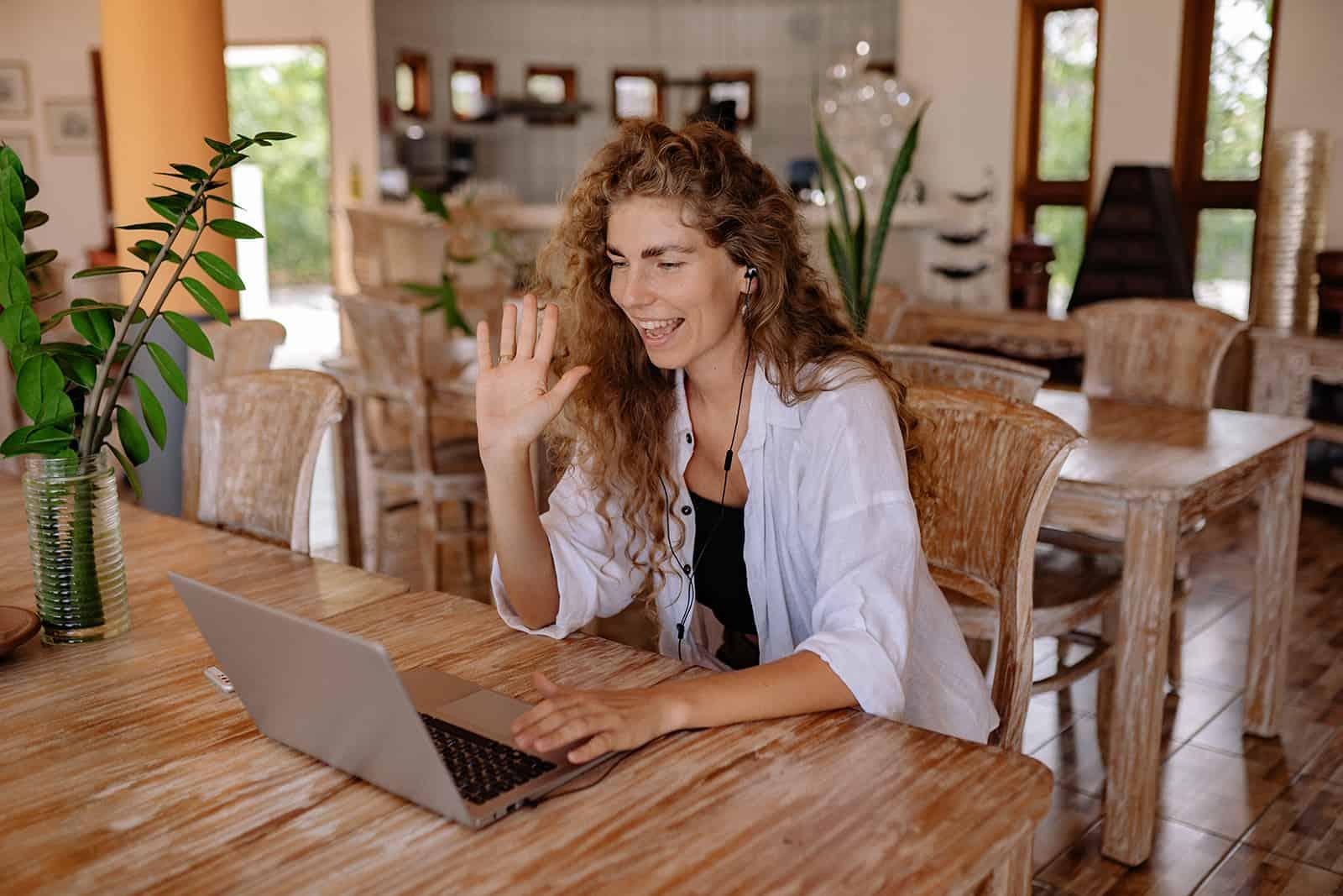 eine Frau, die einen Videoanruf über einen Laptop hat, der mit der Hand winkt
