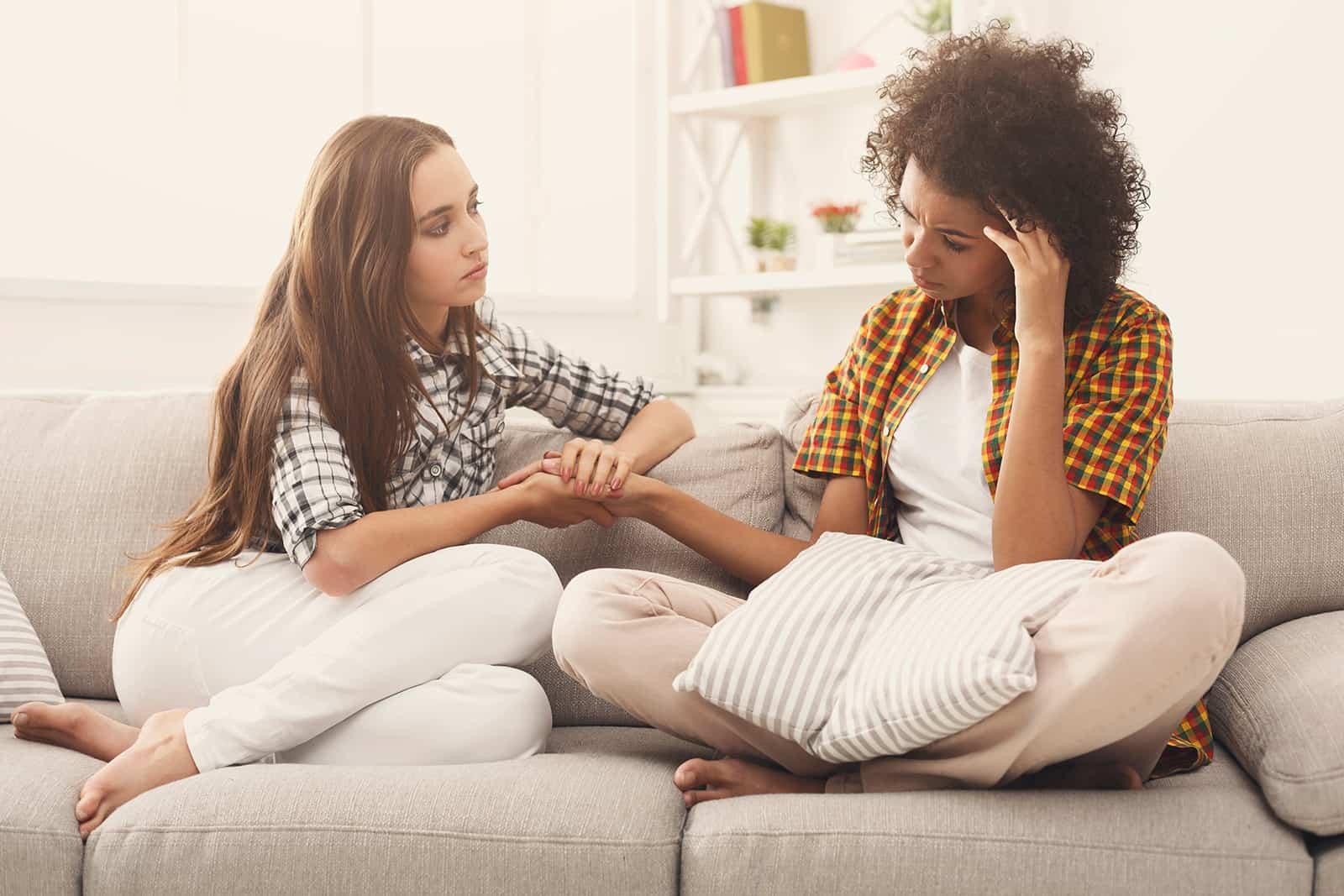 eine Frau tröstet ihre traurige Freundin, die auf der Couch sitzt