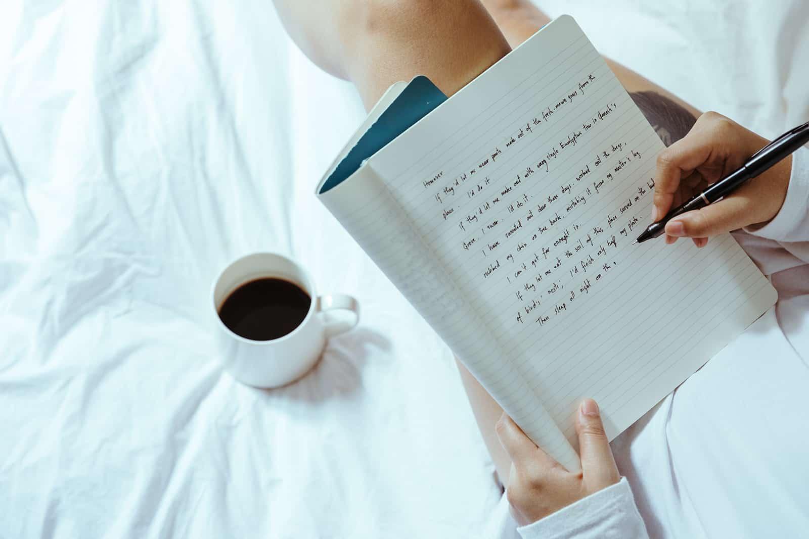 eine Frau, die in ein Notizbuch schreibt, das auf dem Bett sitzt