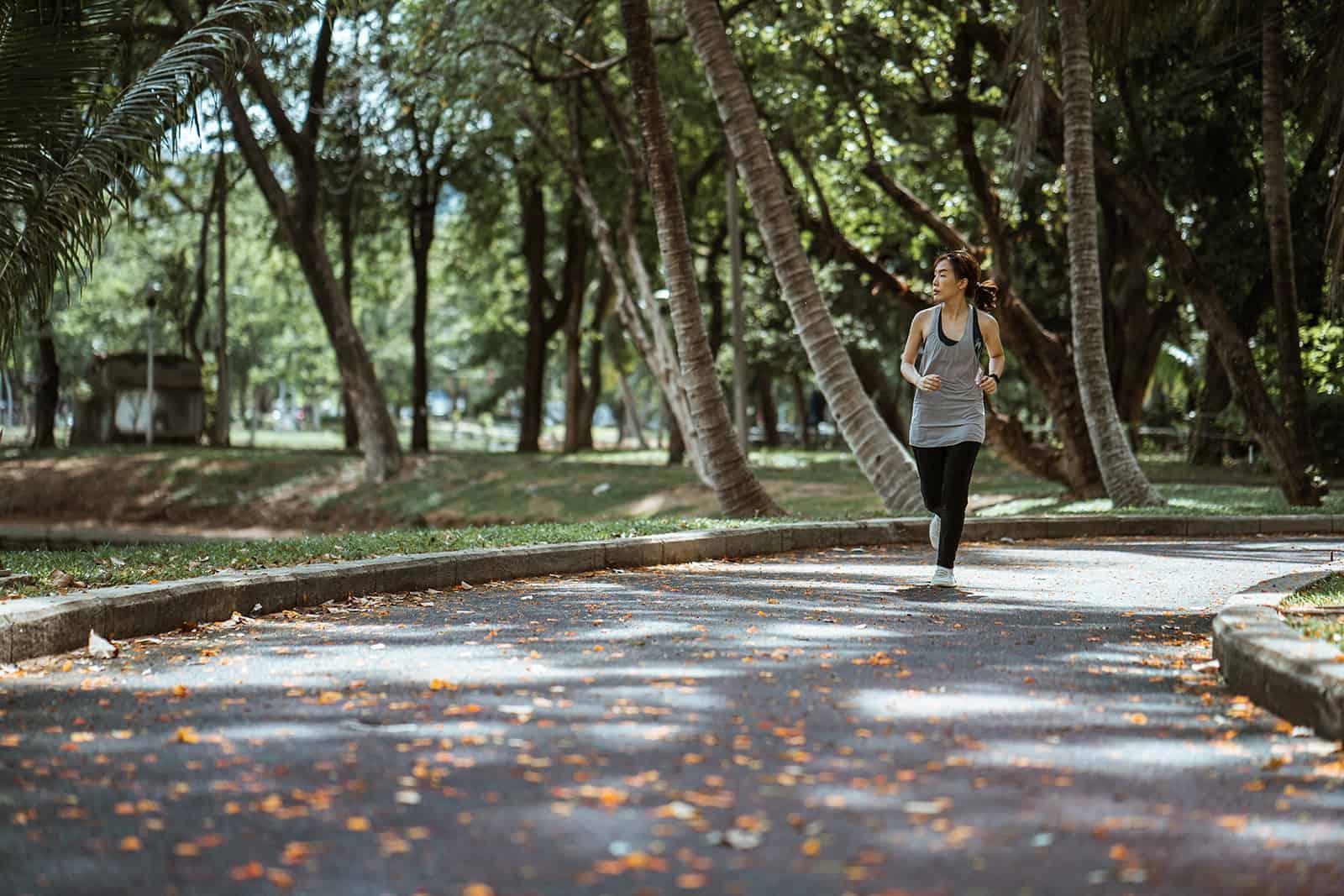 eine Frau, die in einem Park am sonnigen Tag joggt