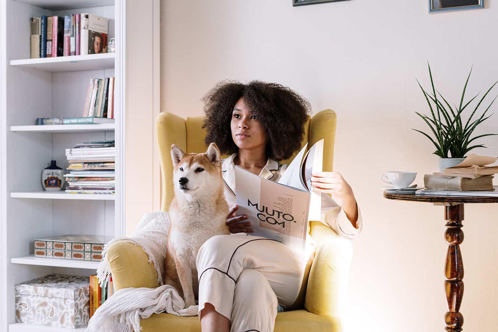 eine Frau, die mit einem Hund in einem Sessel sitzt und eine Zeitschrift hält