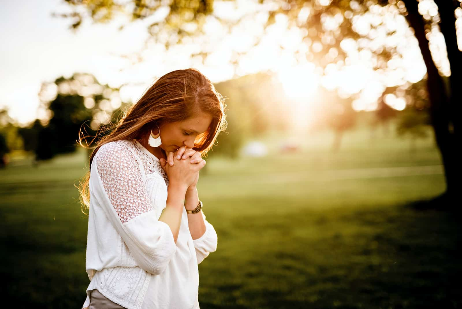 eine Frau, die während des Sonnenuntergangs neben dem Baum betet