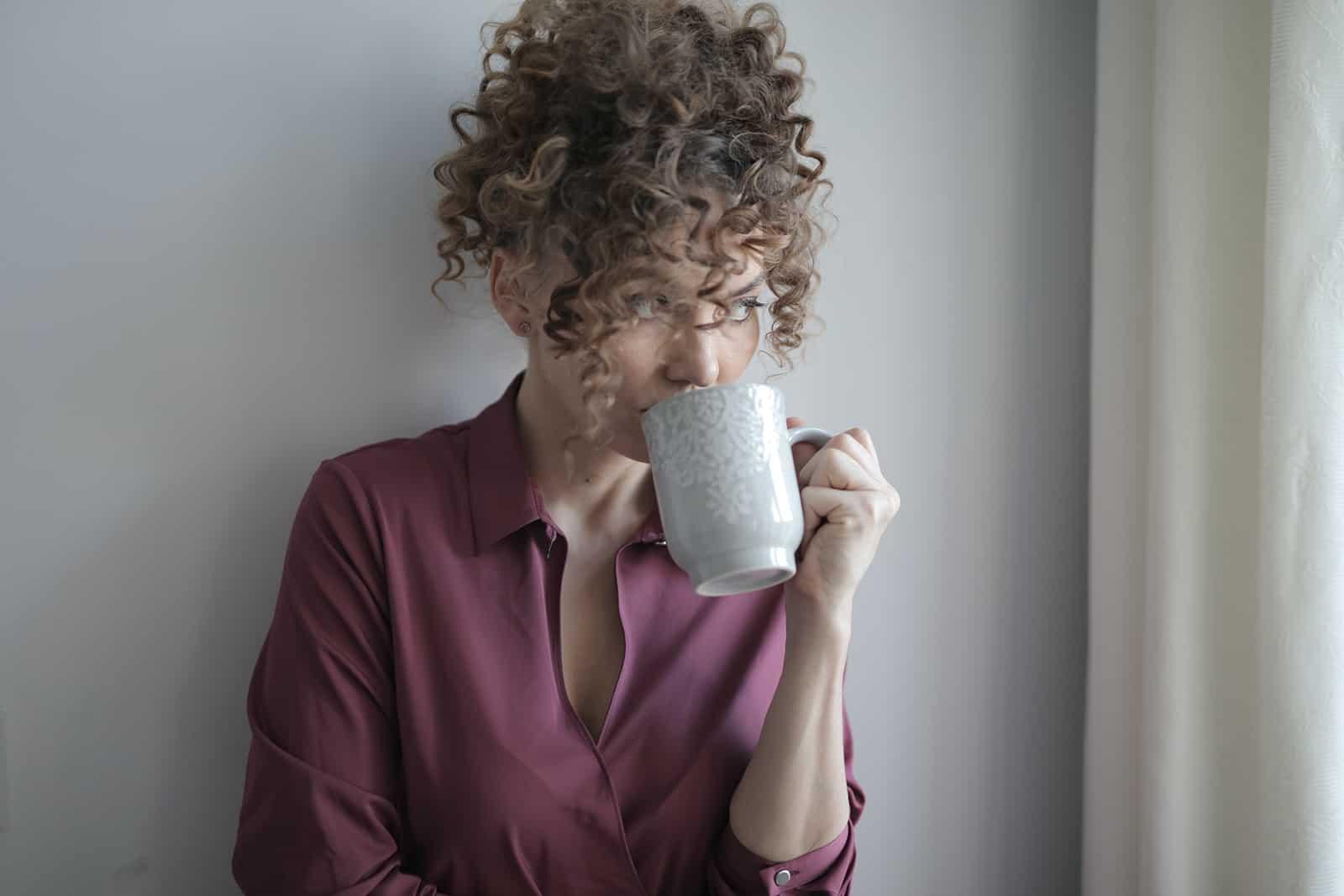 eine Frau, die sich an die Wand lehnt, während sie Kaffee trinkt und nachdenkt