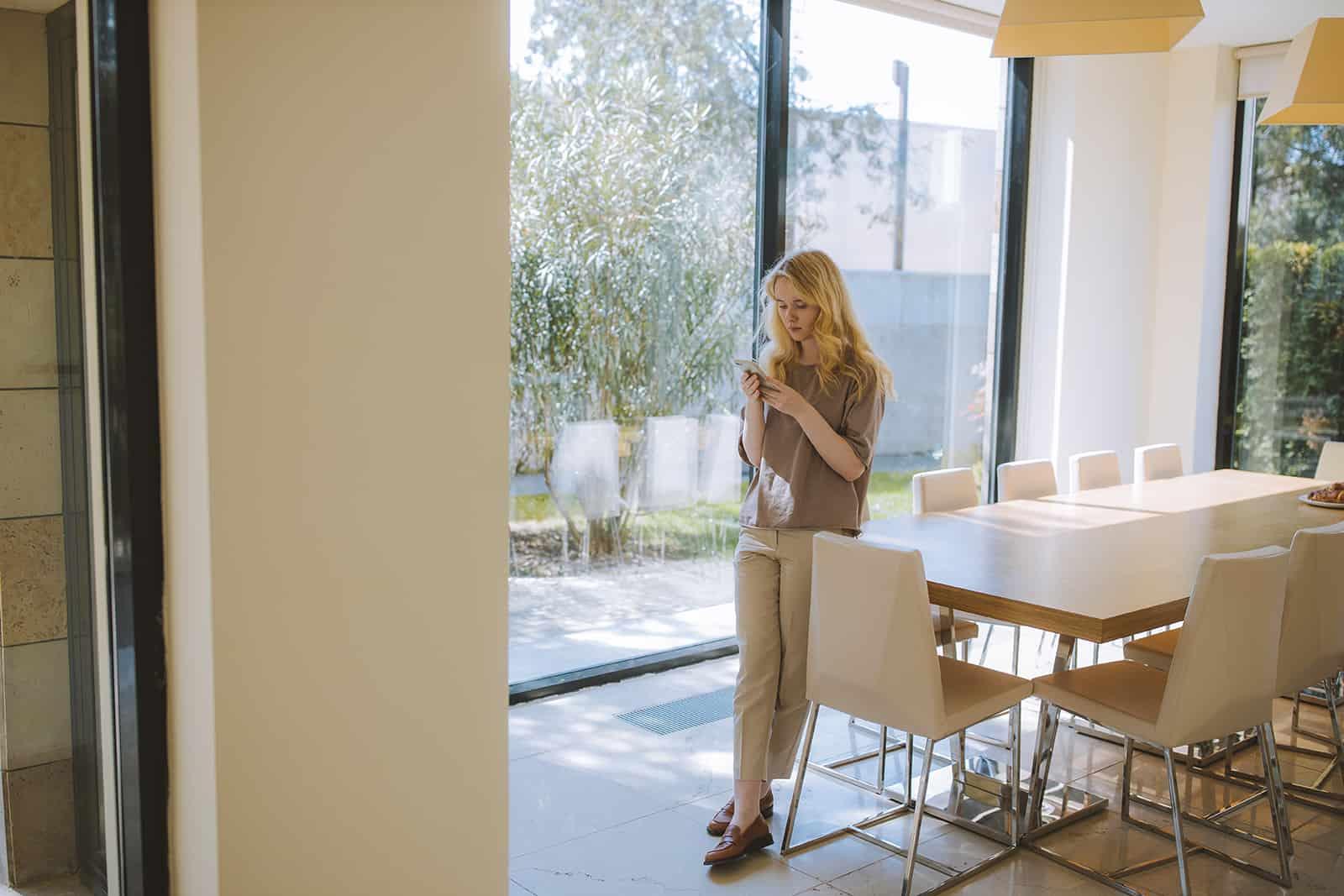 eine Frau, die sich auf den Tisch lehnt und ihr Smartphone benutzt