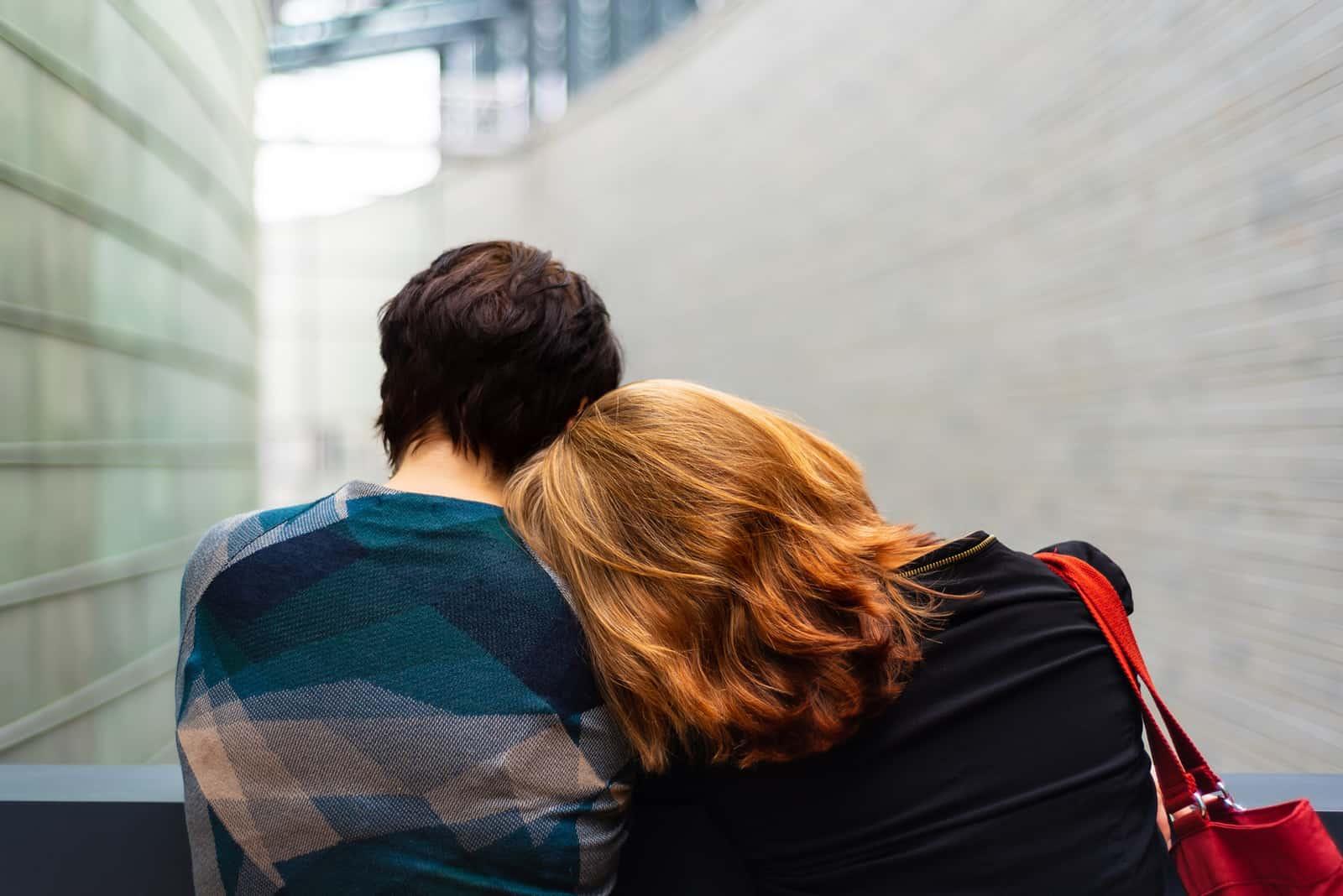 eine Frau, die sich mit dem Kopf auf ihre Freundin stützt, während sie zusammen auf dem Balkon steht