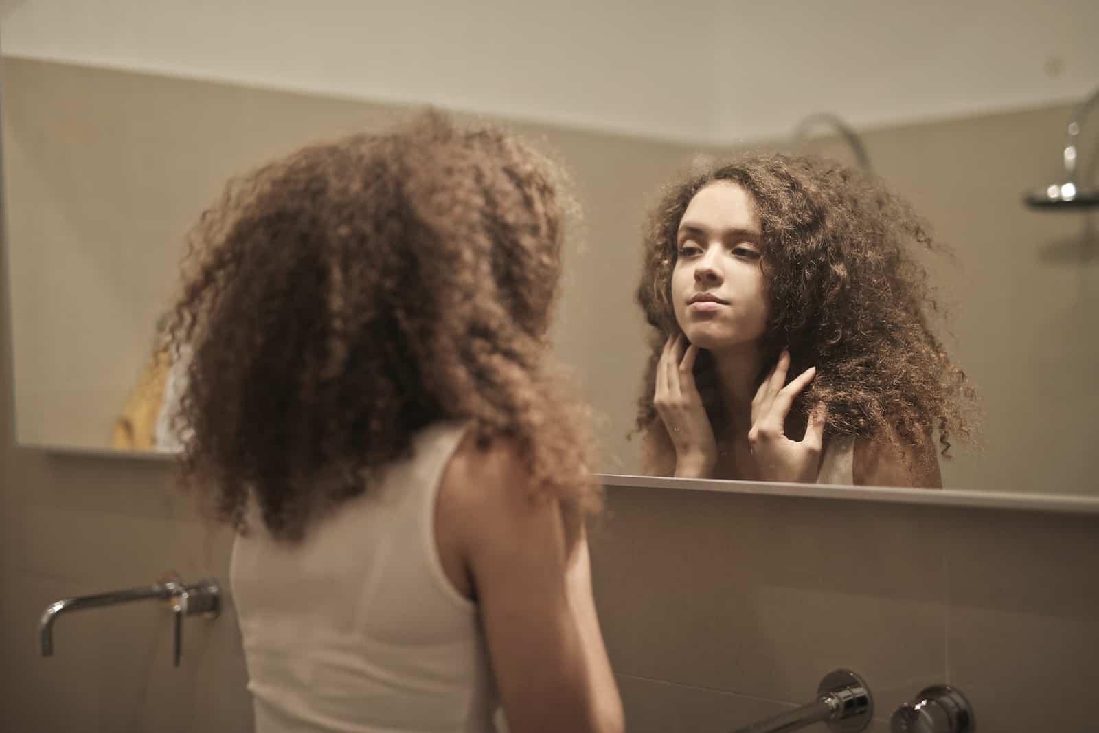 eine Frau, die sich beim Nachdenken in den Spiegel schaut