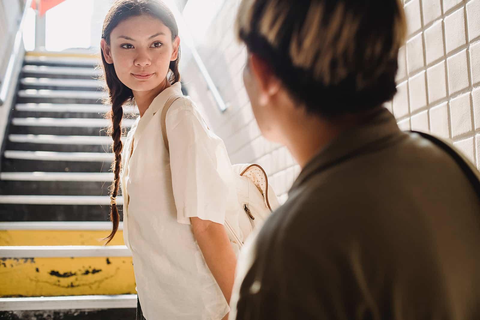 Eine Frau verabschiedet sich von einem Mann, der am Fuß der Treppe steht