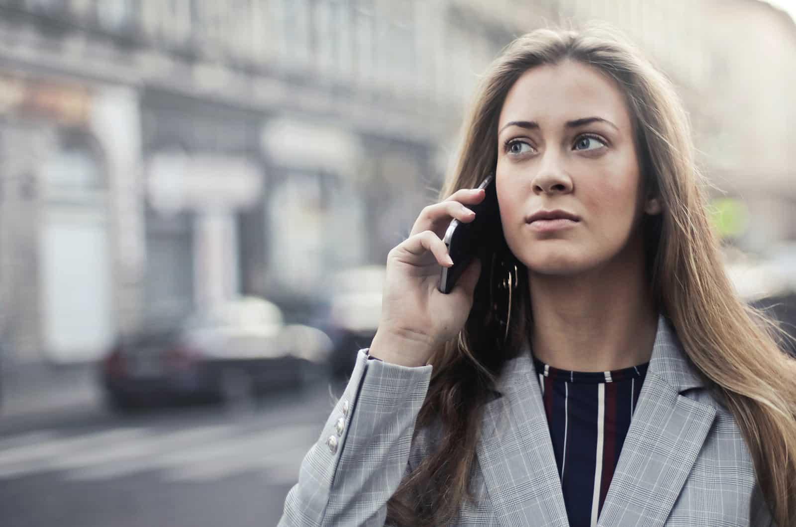 eine Frau, die versucht, einen Freund am Telefon zu erreichen, während sie durch die Stadt geht