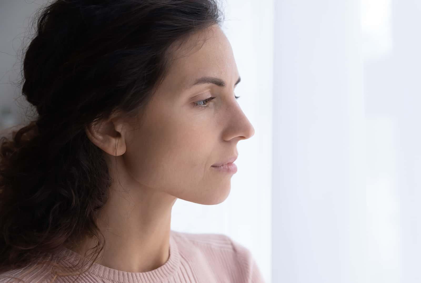eine Frau in einem rosa Pullover, die durch das Fenster schaut