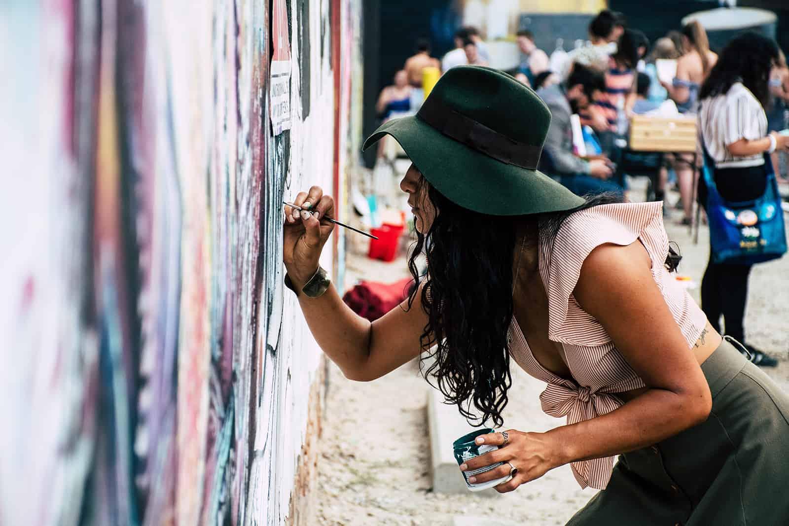 eine Frau, die mit einem Pinsel an die Wand malt