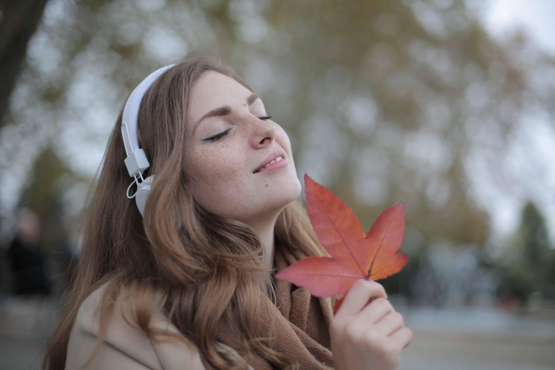 eine Frau mit Kopfhörern, die Musik hört und ein rotes Blatt hält