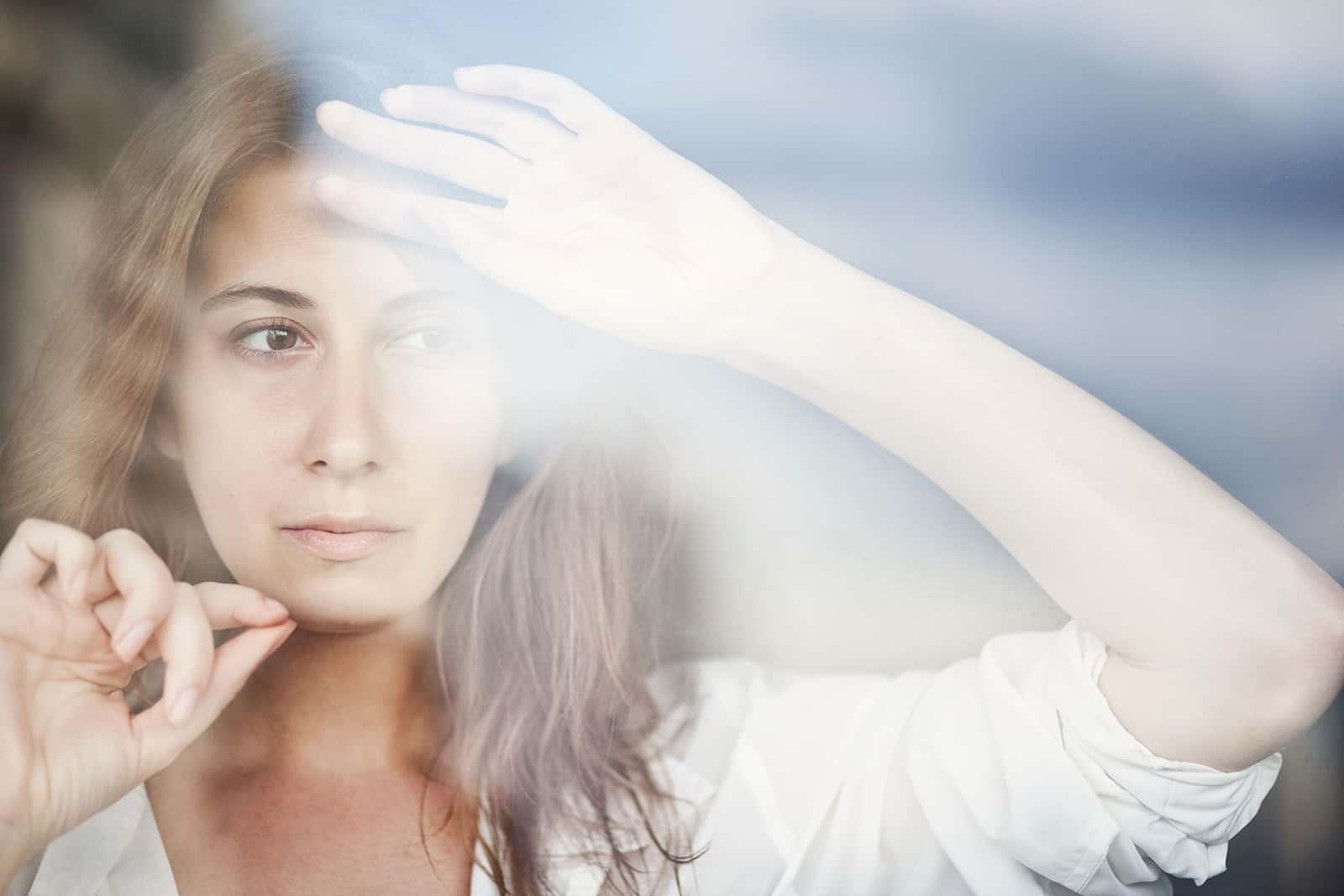 eine Frau mit braunen Haaren, die beim Nachdenken die Hände an das Fenster lehnt