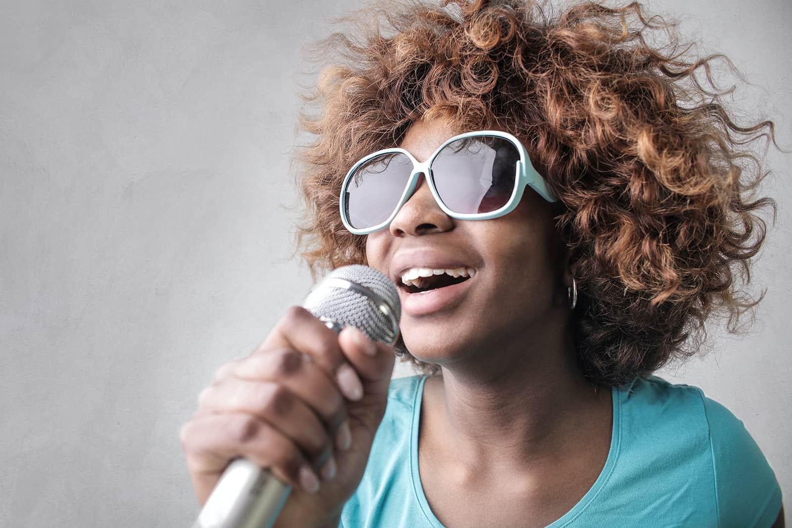 eine Frau, die ein Mikrofon hält und ein Lied singt