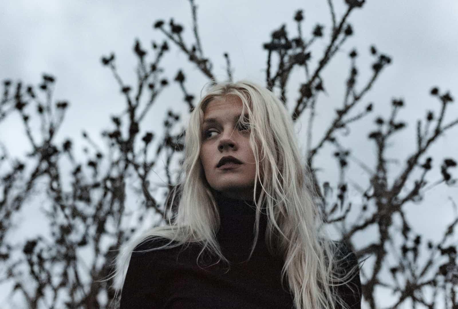 eine Frau mit langen blauen Haaren, die beiseite schaut, steht nahe dem Baum