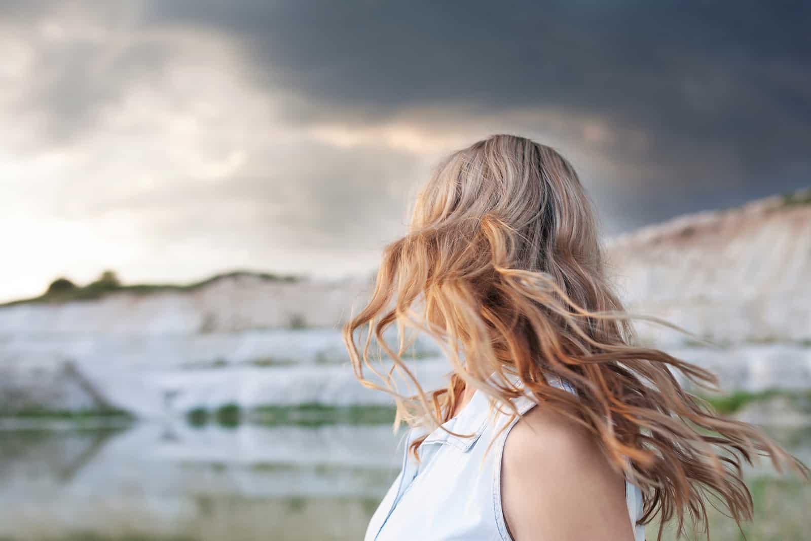 eine Frau mit langen blonden Haaren, die im Wind gegen den Gewitterhimmel stehen