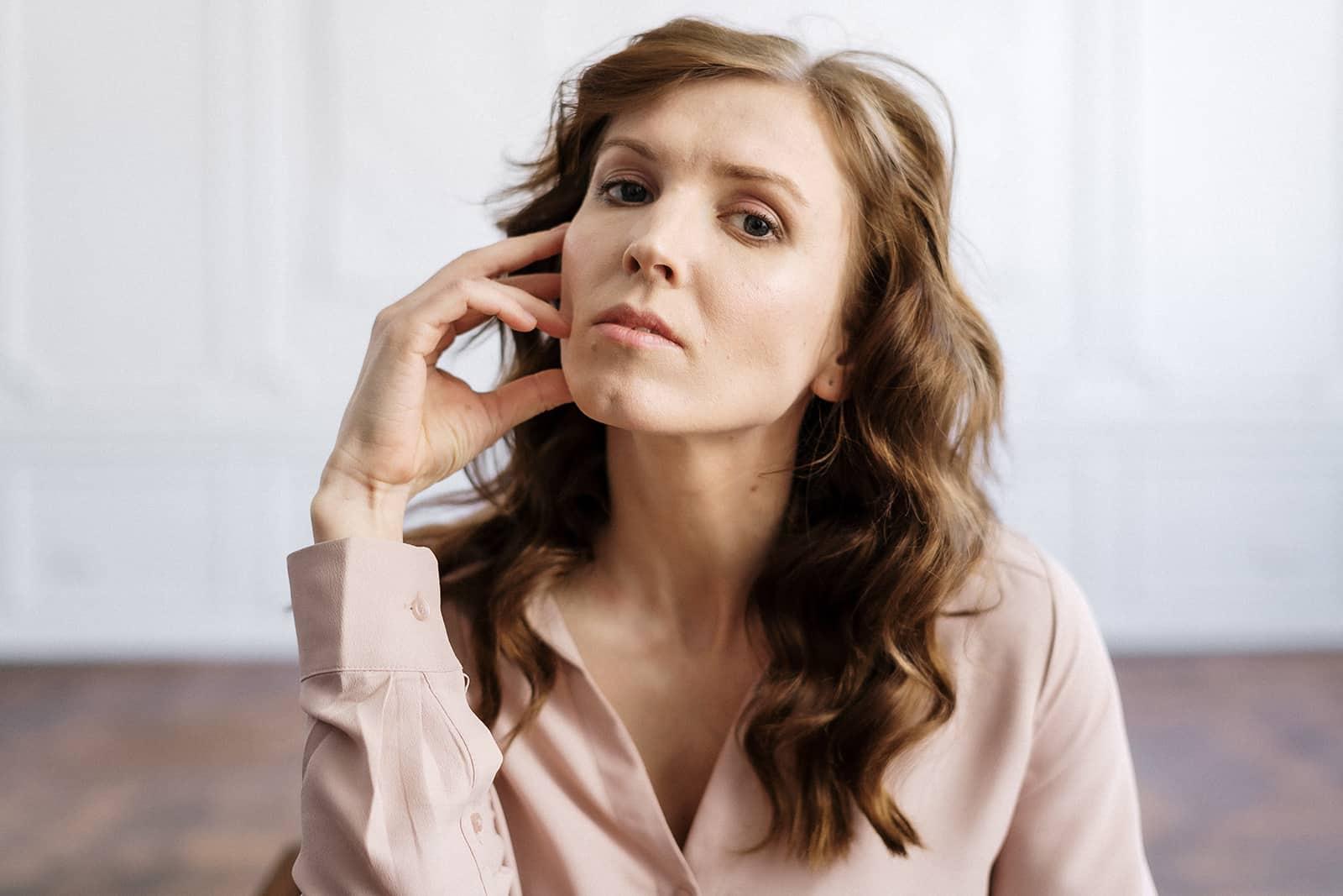 eine Frau mit langen braunen Haaren denkt nach und berührt ihr Gesicht mit einer Hand