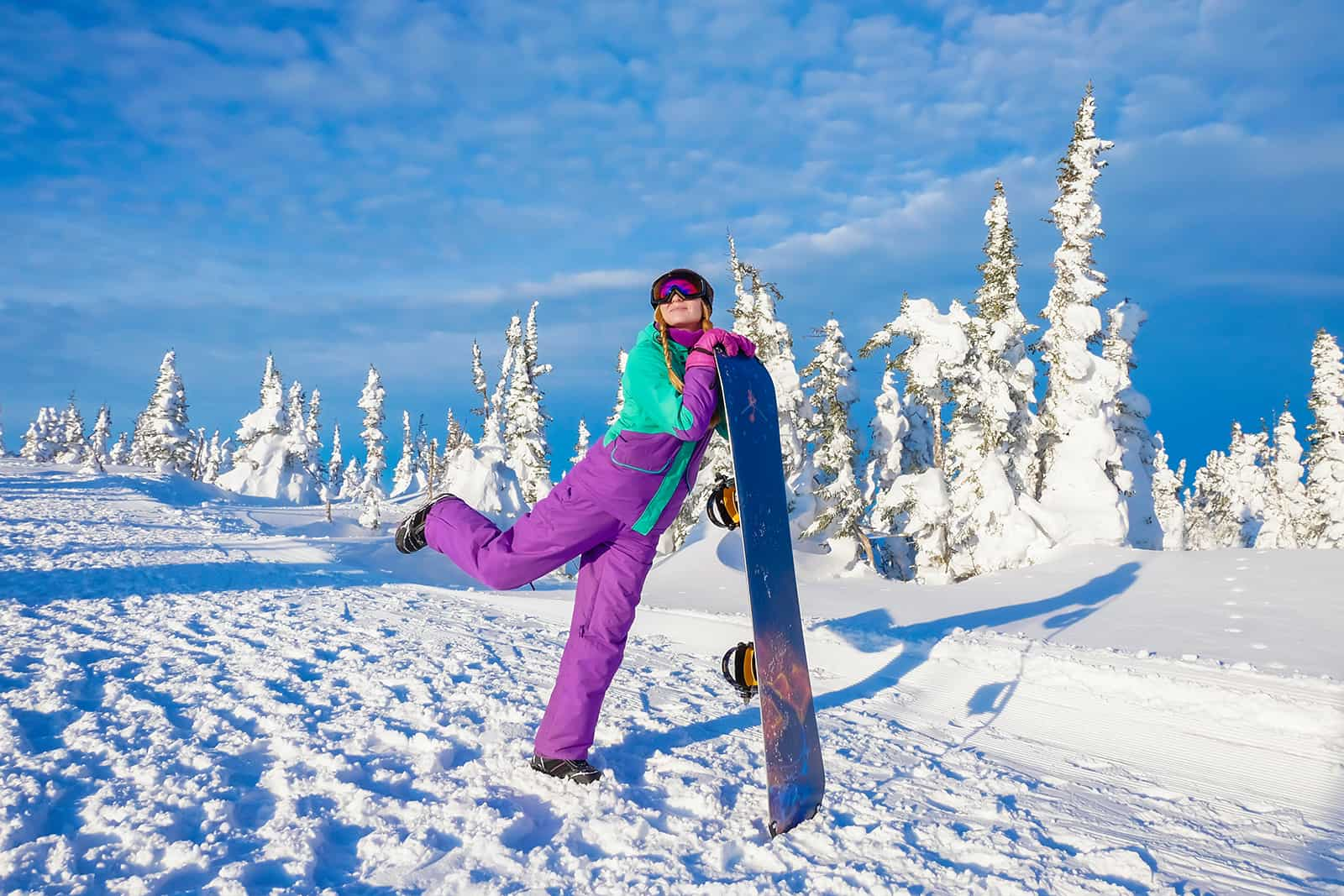 eine Frau, die mit einem Skateboard für Fotografie posiert, während sie auf dem Schnee steht