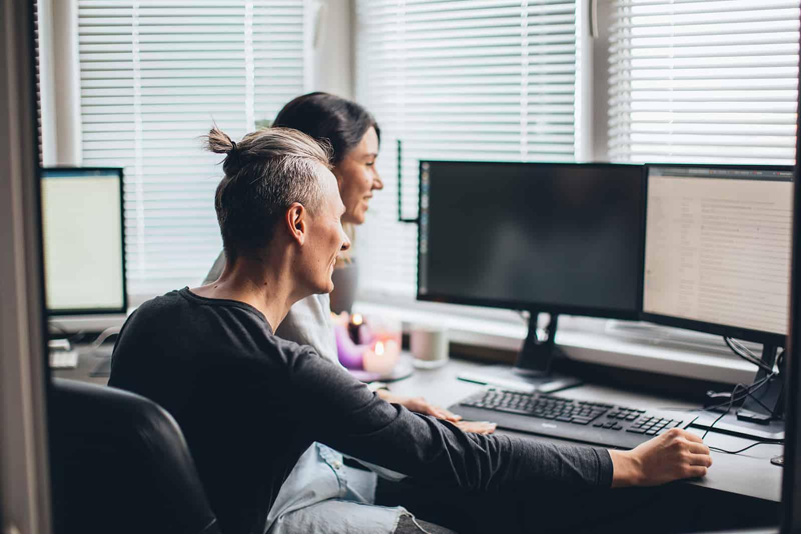 Eine Frau sitzt auf dem Schoß ihres Freundes, während er ihr seinen Job im Büro vorstellt