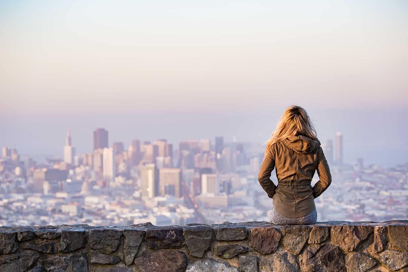 eine Frau sitzt auf der Felswand gegenüber der Stadt