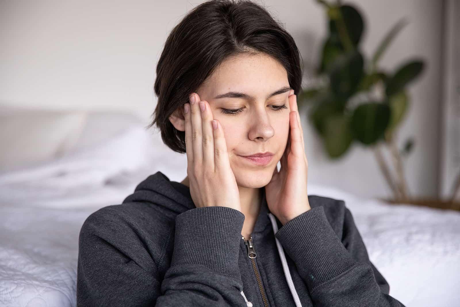 eine Frau, die neben dem Bett sitzt und den Kopf mit den Händen berührt
