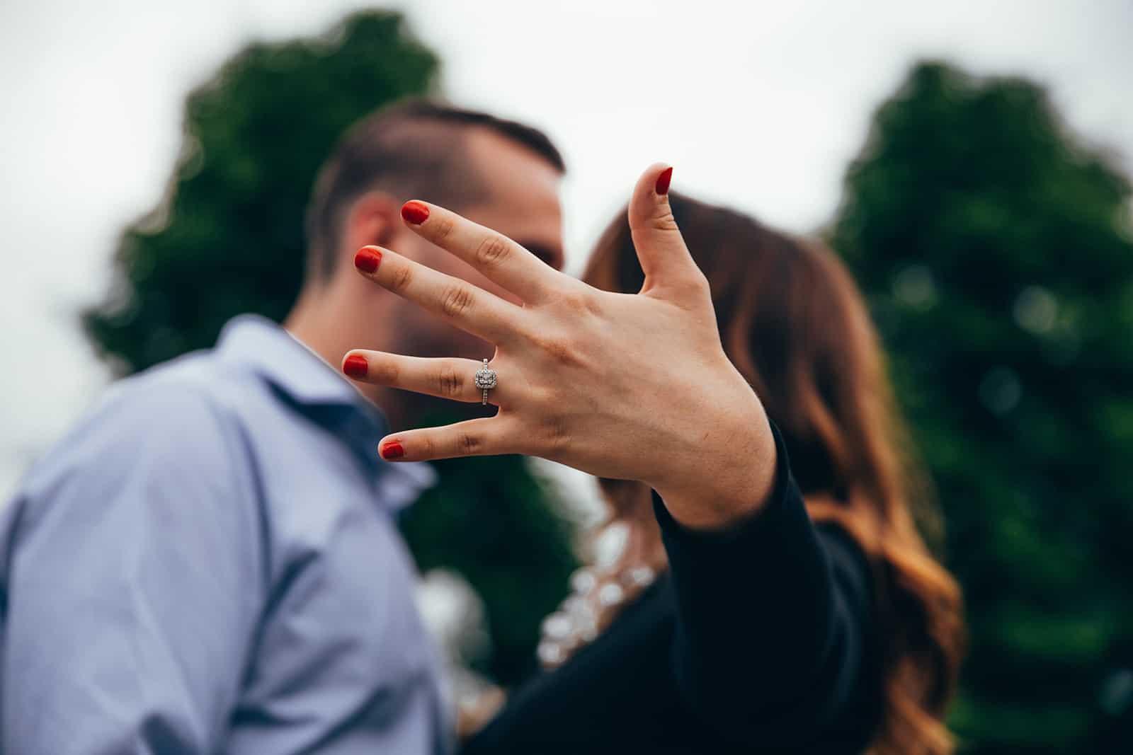Eine Frau zeigt ihren Ring an einer Hand, während sie sich mit einem Mann küsst