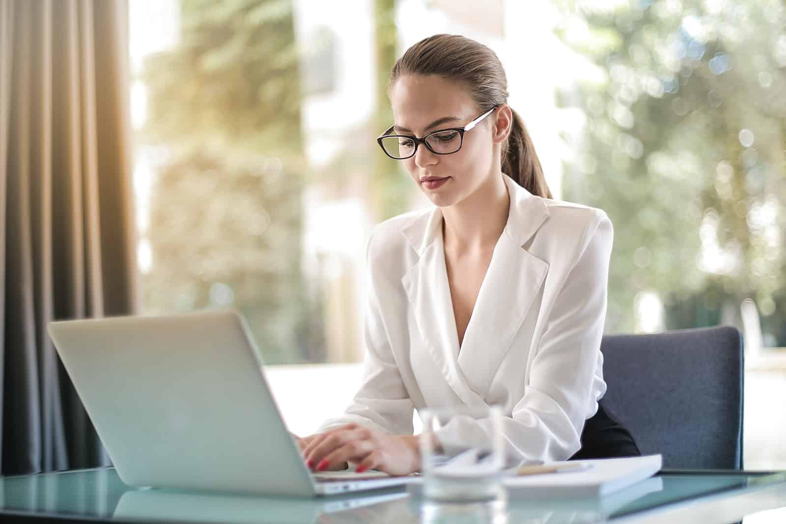 eine Geschäftsfrau, die auf dem Laptop tippt, während sie im Büro sitzt