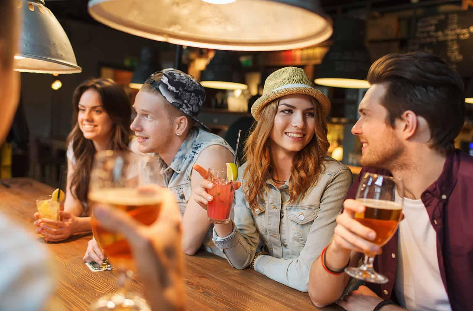 Eine Gruppe von Leuten, die in der Bar rumhängen und Bier trinken