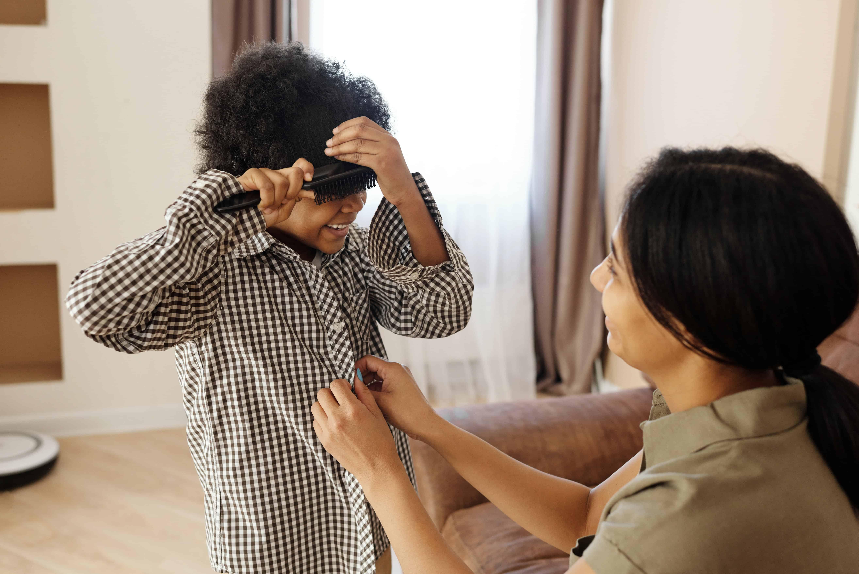 Eine Mutter knöpft das Hemd ihres Sohnes zu, während er sich die Haare bürstet