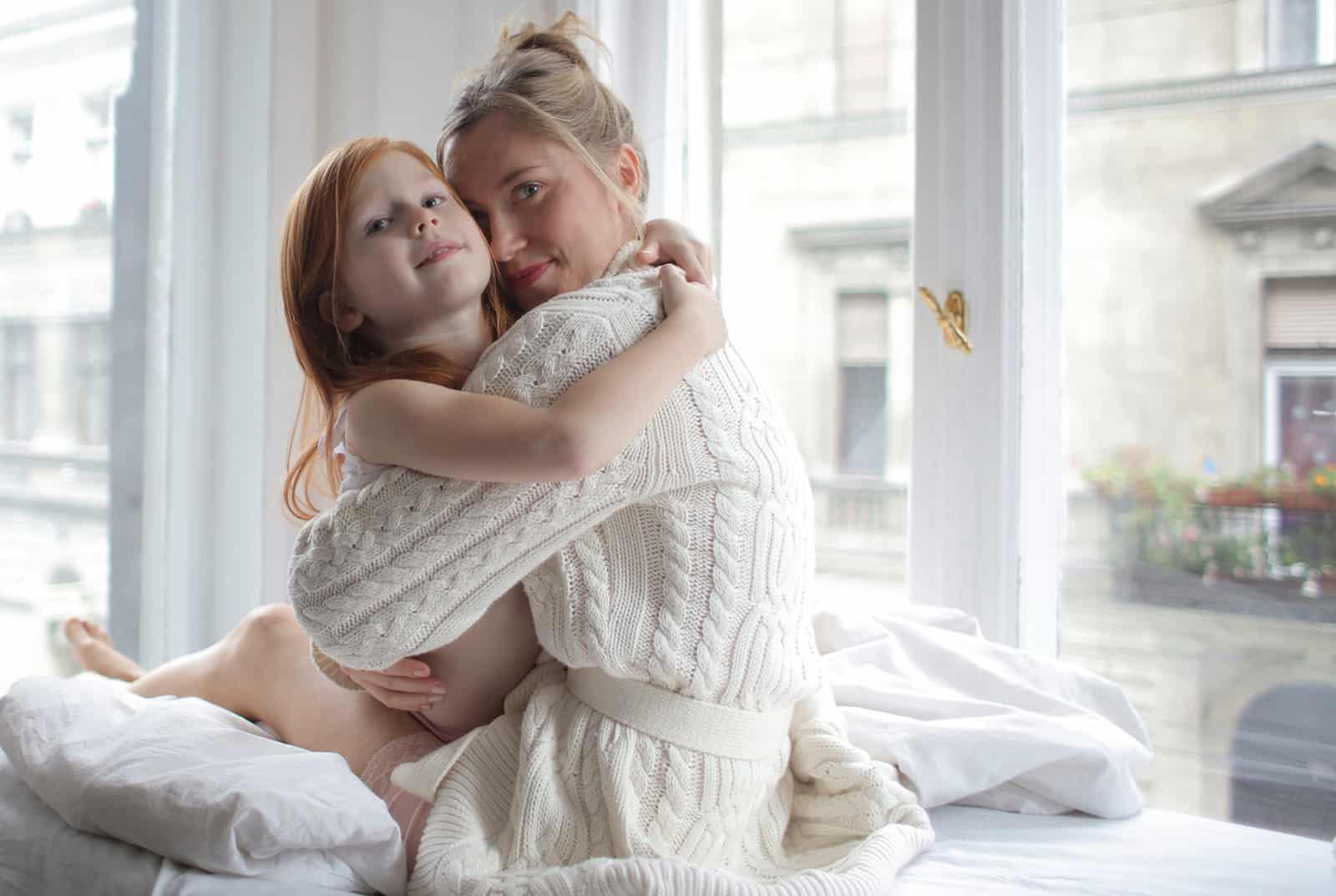 Eine Mutter umarmt ihre kleine Tochter, die auf dem Bett sitzt