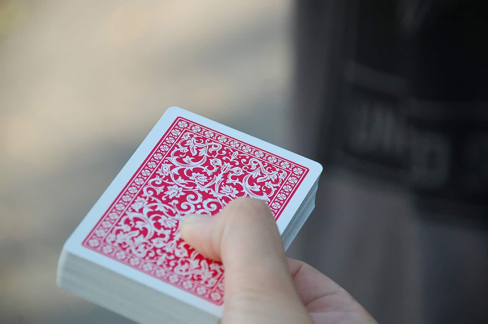 eine Person, die ein Kartenspiel in der Hand hält