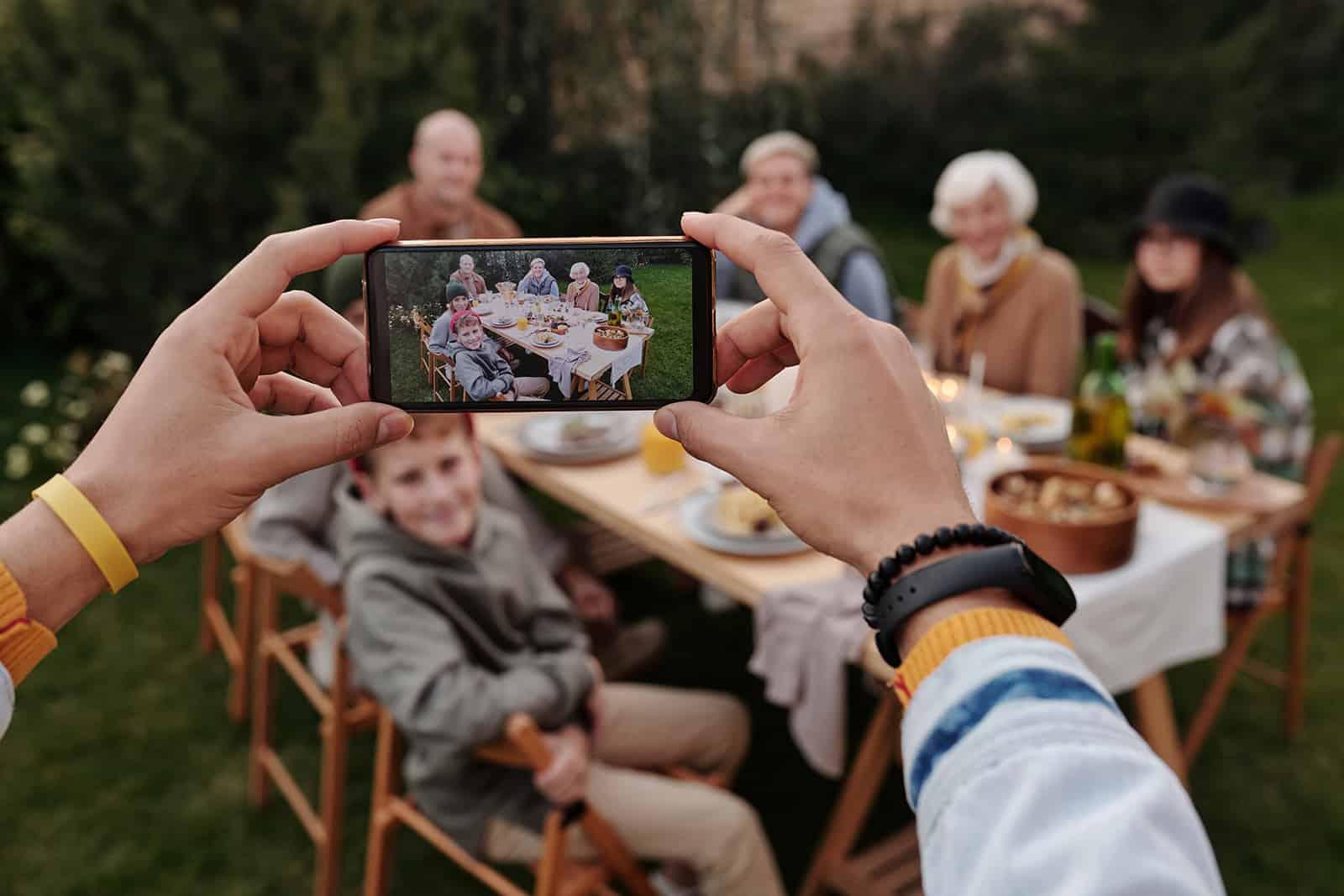 eine Person, die ein Foto einer Familie macht, die am Tisch in einem Hof sitzt