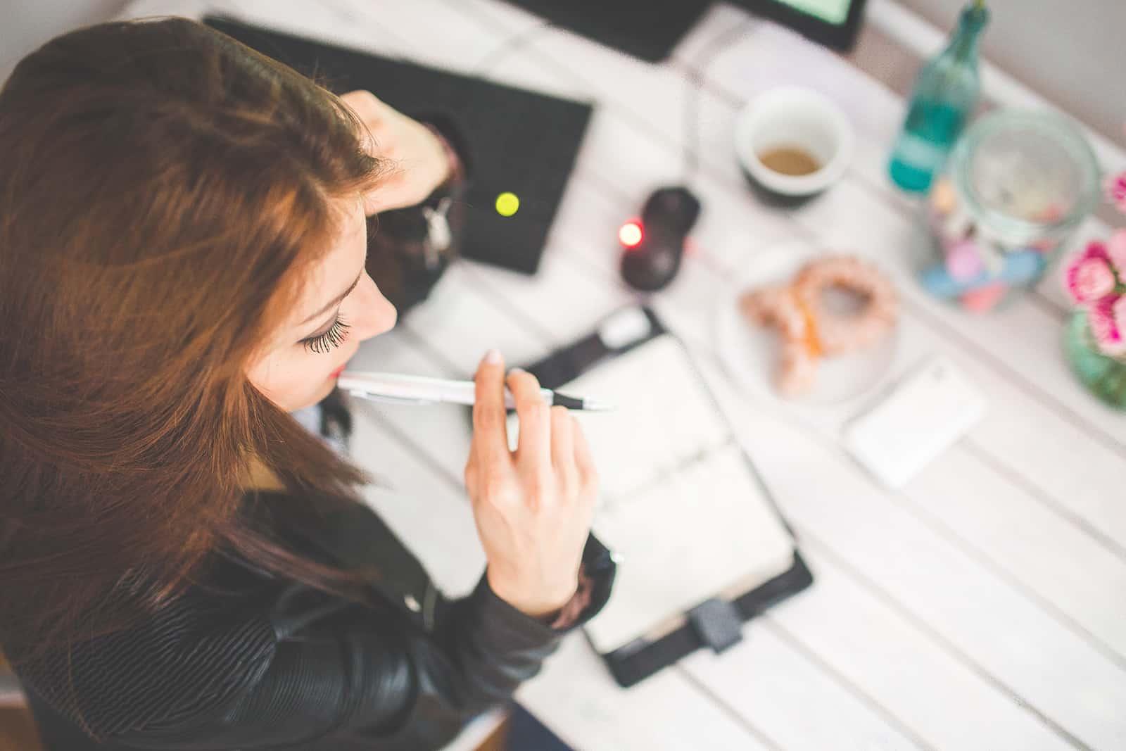 eine abgelenkte Frau, die einen Stift hält, während sie am Schreibtisch arbeitet
