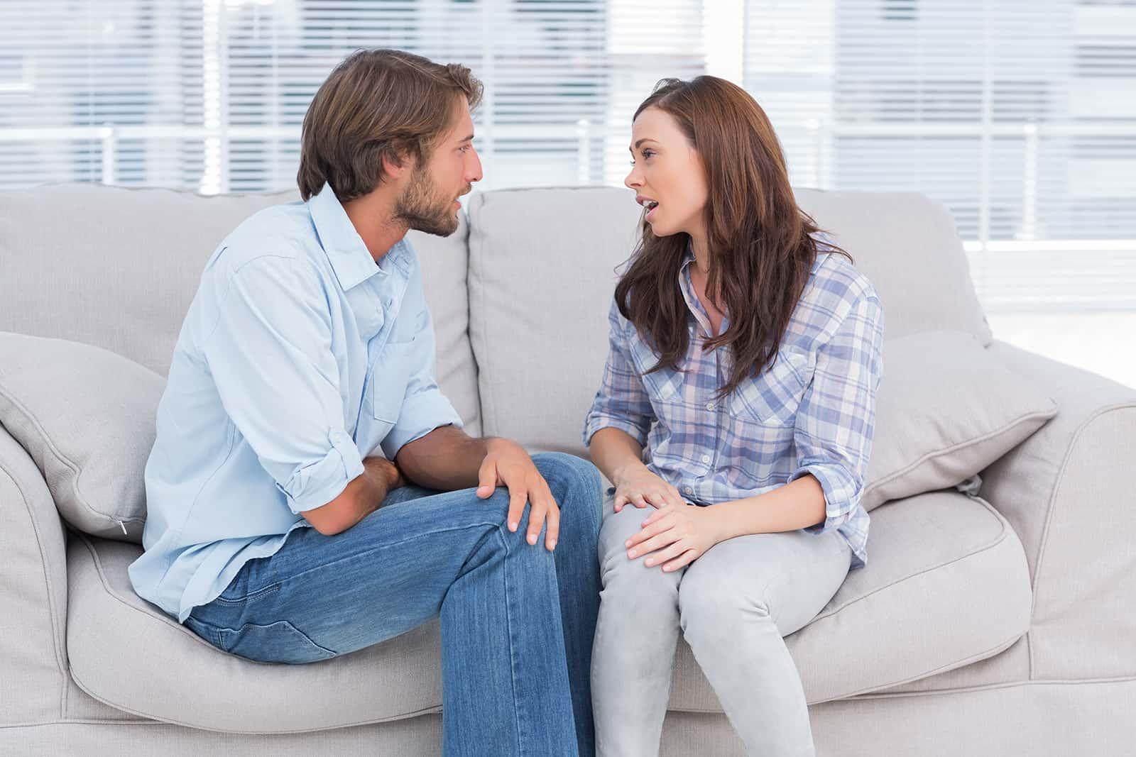 eine besorgte Frau, die mit einem Mann spricht, während sie zusammen auf der Couch sitzt