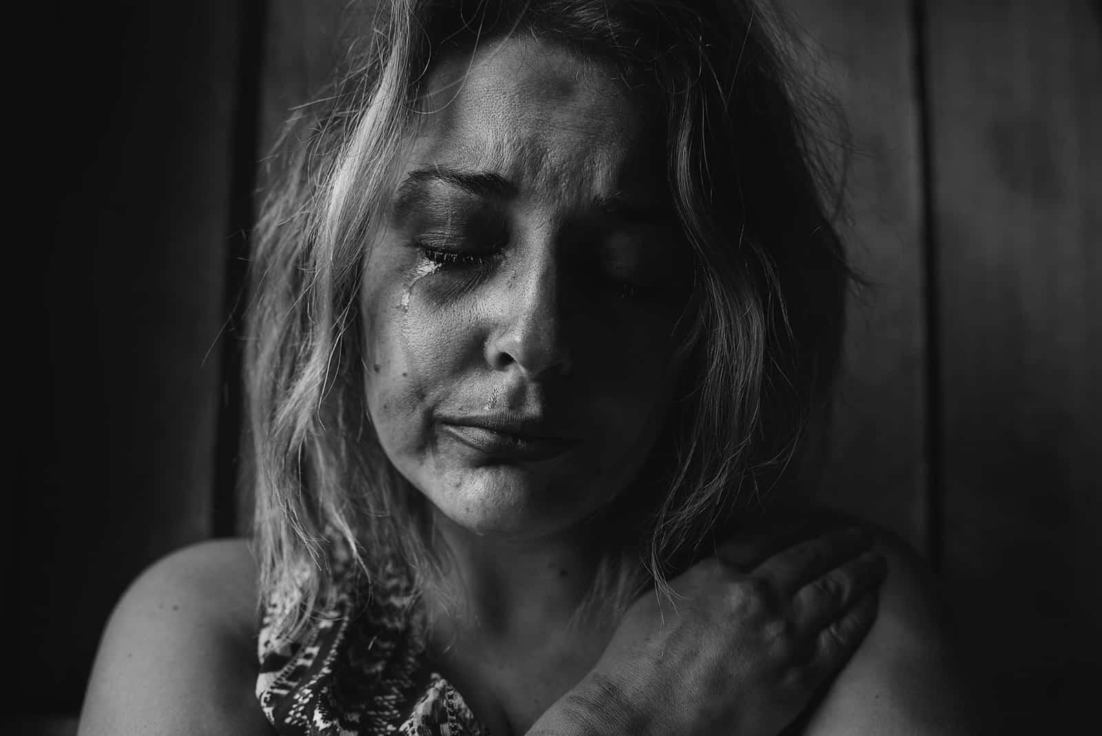 eine depressive Frau, die mit geschlossenen Augen weint