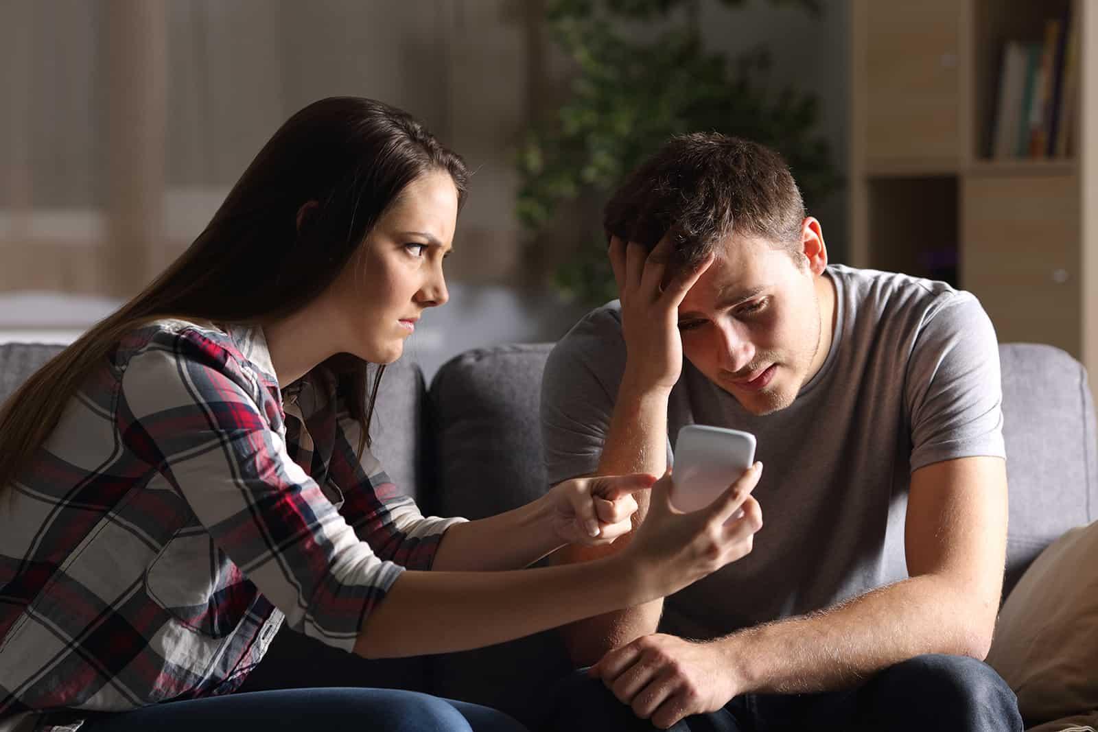 Eine eifersüchtige Frau zeigt ihrem verzweifelten Freund ein Smartphone und bittet um eine Erklärung